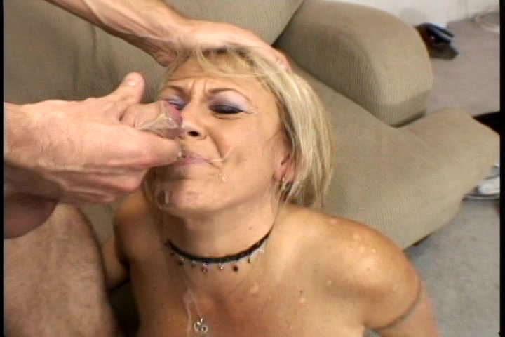 De milf zuigt aan zijn stijve lul tot hij haar gezicht helemaal vol sperma spuit